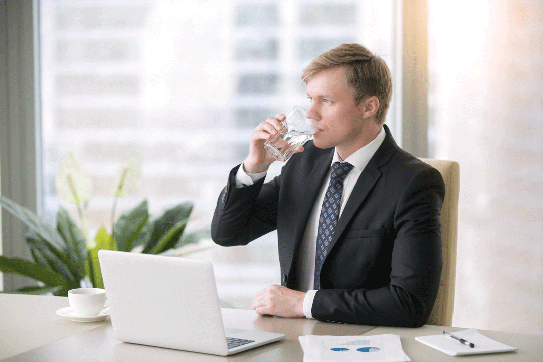 Man sat infront of laptop drinking from glass of water