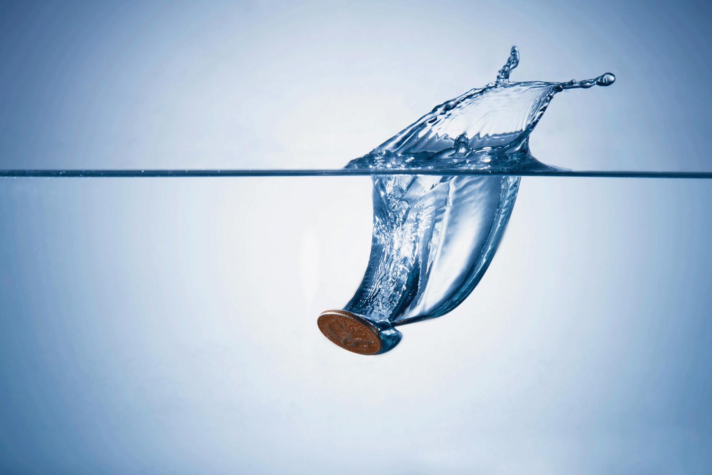 Coin splashing into pool of water