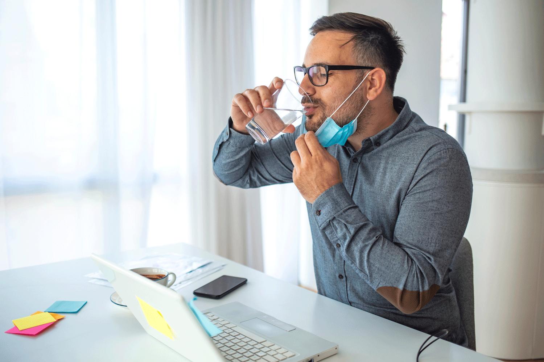 Man sat as desek pulling mask down to drink water