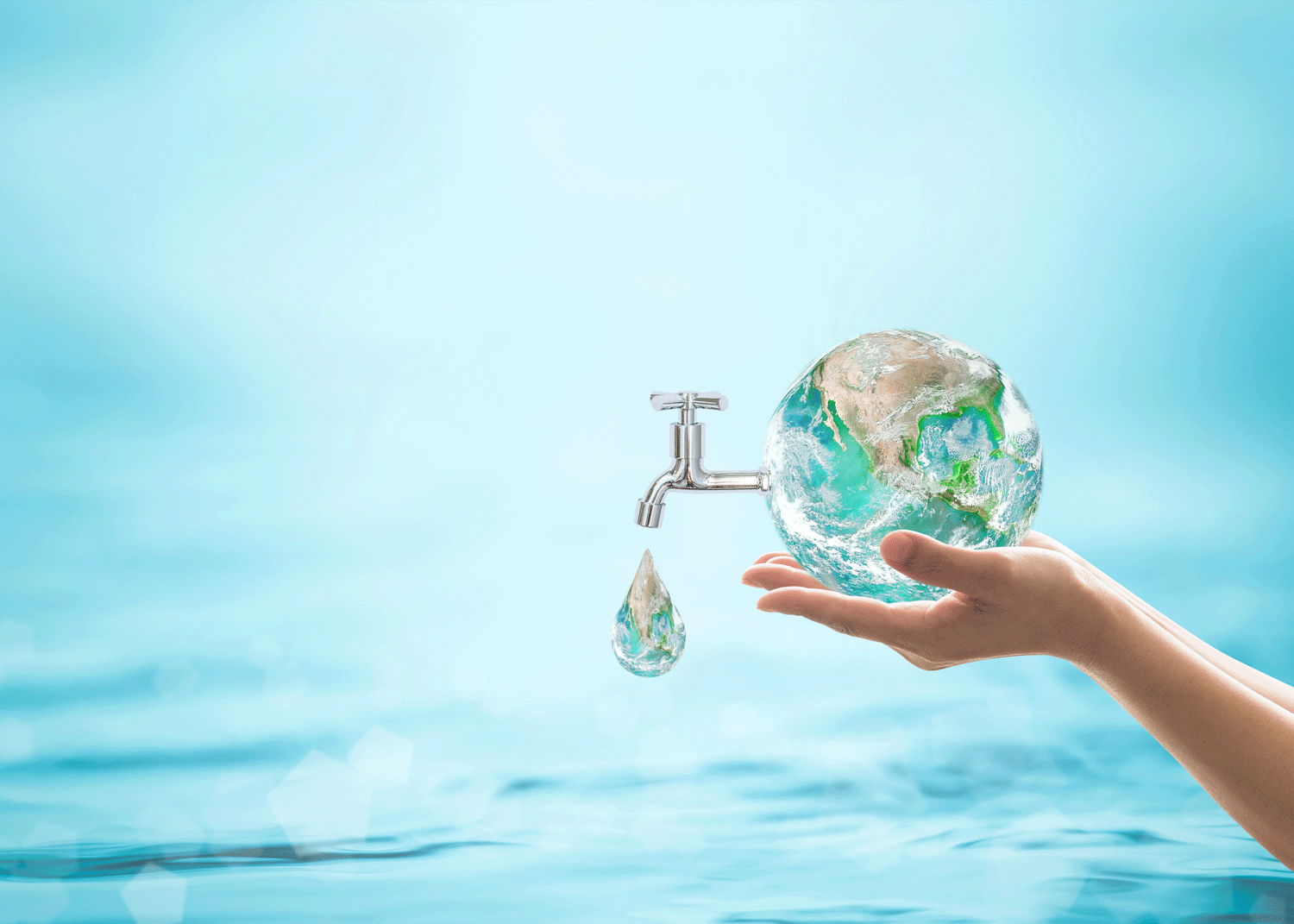 Hand holiday globe above water